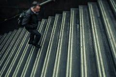 Hombre anónimo que camina encima de las escaleras foto de archivo