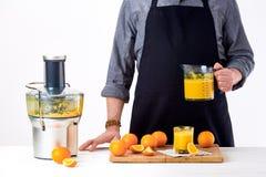 Hombre anónimo que lleva un delantal, preparando el zumo de naranja recién hecho, usando el juicer eléctrico moderno, concepto sa Fotos de archivo libres de regalías