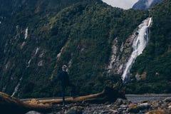 Hombre anónimo que mira el acantilado y el agua que cae foto de archivo libre de regalías