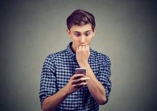 Hombre ansioso infeliz que mira su teléfono elegante Fotografía de archivo