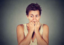 Hombre ansioso que muerde sus fingeres de los clavos freaking hacia fuera Imagen de archivo