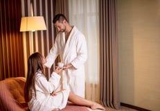 Hombre apacible hermoso joven que ofrece una taza de té a su novia fotos de archivo libres de regalías