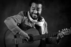 Hombre apasionado del Afro que toca la guitarra imagen de archivo libre de regalías