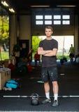 Hombre apto con la situación cruzada brazos en Healthclub Fotografía de archivo libre de regalías