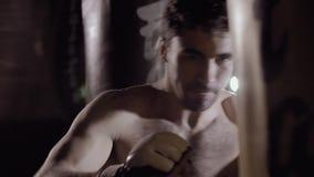Hombre apto concentrado que se resuelve batiendo el bolso del boxeo almacen de metraje de vídeo