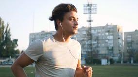 Hombre apto de la raza mixta de los jóvenes que escucha la música y que se resuelve corriendo en pista urbana del estadio almacen de video