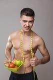 Hombre apto del vegano con la cinta métrica y la comida sana Fotos de archivo