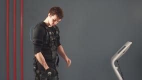 Hombre apto en el traje muscular eléctrico del estímulo que se coloca con pesas de gimnasia almacen de metraje de vídeo