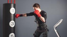 Hombre apto en guantes de boxeo durante el entrenamiento boxeador en traje del estímulo eléctrico en gimnasio metrajes