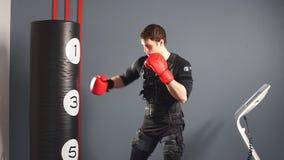 Hombre apto en guantes de boxeo durante el entrenamiento boxeador en traje del estímulo eléctrico en gimnasio almacen de video