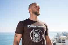 Hombre apto en la camisa de Brown Kettlebell Foto de archivo libre de regalías