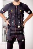 Hombre apto en la electro máquina muscular del estímulo imagen de archivo