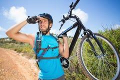 Hombre apto que camina abajo del rastro que sostiene la bici de montaña Fotos de archivo