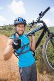 Hombre apto que camina abajo del rastro que sostiene la bici de montaña que sonríe en la cámara Imagen de archivo libre de regalías