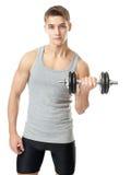 Hombre apto que ejercita con pesas de gimnasia Foto de archivo