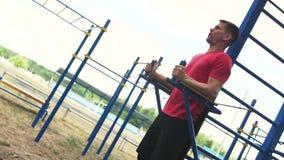 Hombre apto que entrena a los músculos abdominales en gimnasio del aire libre almacen de metraje de vídeo