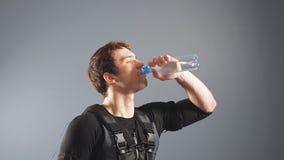 Hombre apto que lleva la electro agua de la bebida del traje del estímulo después de entrenar almacen de video