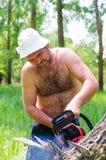 Hombre apto que lleva una motosierra en arbolado fotografía de archivo libre de regalías