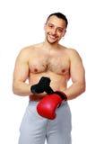 Hombre apto que pone sus guantes de boxeo Foto de archivo