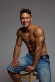 Hombre apto sonriente que se sienta en un taburete de madera Imagen de archivo libre de regalías