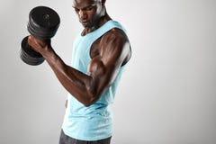 Hombre apto y joven que se resuelve con pesa de gimnasia pesada imágenes de archivo libres de regalías