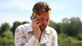 Hombre apuesto con la barba en la camisa que coloca hablar al aire libre en su teléfono almacen de metraje de vídeo