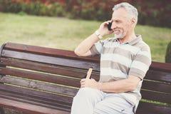 Hombre apuesto encantado que habla en el teléfono Foto de archivo