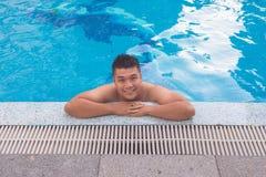 Hombre apuesto que sonríe y que se relaja en piscina Foto de archivo libre de regalías