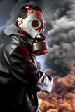 Hombre armado con la careta antigás sobre fondo de la explosión Fotografía de archivo