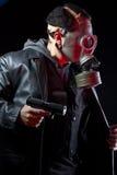 Hombre armado con la careta antigás y el arma Imagenes de archivo