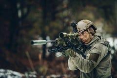 Hombre armado en camuflaje con el arma del francotirador Foto de archivo libre de regalías