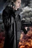 Hombre armado en fondo con la explosión imagenes de archivo
