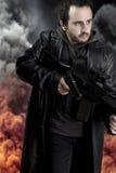 Hombre armado en fondo con la explosión foto de archivo