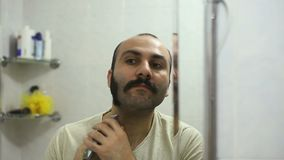 Hombre armenio que afeita la barba usando la máquina de afeitar eléctrica del condensador de ajuste almacen de metraje de vídeo