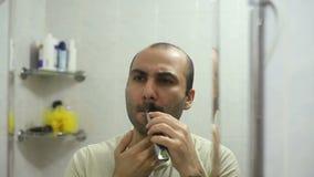 Hombre armenio que afeita la barba usando la máquina de afeitar eléctrica del condensador de ajuste almacen de video