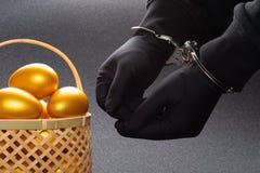 Hombre arrestado en esposas delante de la cesta con los huevos del oro fotografía de archivo libre de regalías