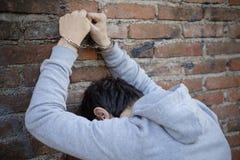 Hombre arrestado en esposas en la pared foto de archivo libre de regalías