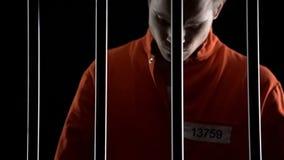 Hombre arrestado trastornado en el traje anaranjado detrás de barras de la prisión, juicio de la pena de muerte imagen de archivo