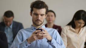 Hombre ascendente cercano usando el teléfono durante rotura de la conferencia almacen de video