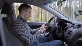 Hombre asentado en coche con la tableta digital metrajes