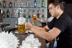 Hombre asentado en la barra con una jarra de cerveza grande de la cerveza Fotos de archivo libres de regalías