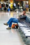 Hombre asentado que habla en el teléfono en un aeropuerto Imágenes de archivo libres de regalías