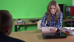 Hombre asesor del cliente del encargado de sexo femenino del servicio de reparación del ordenador con el ordenador portátil quebr metrajes