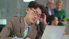 Hombre asiático cansado que trabaja en el ordenador portátil en la oficina almacen de video