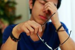 Hombre asiático con el dolor de ojo que sostiene los vidrios imagen de archivo