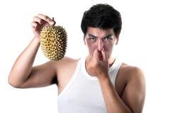 Hombre asiático con el mún olor del durian en el fondo blanco fotos de archivo