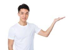 Hombre asiático con la mano que muestra un lado en blanco Fotos de archivo