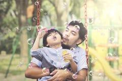Hombre asiático con las burbujas de jabón del niño que soplan Imágenes de archivo libres de regalías