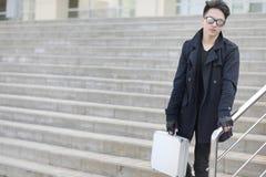 Hombre asiático con una maleta del metal en la ciudad Ca asiático y de plata Imágenes de archivo libres de regalías