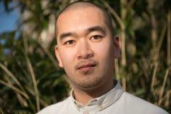 Hombre asiático confiado que mira la cámara contra fondo de lámina imagen de archivo libre de regalías